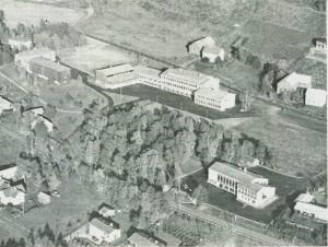 Skoleanlegget på Bell, gamleskolen t.v., nyskolen i sentrum. Samfunnshuset «Gimle» nederst t.h. Foto: Ragde.