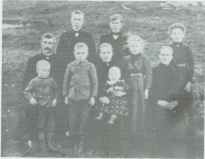 Marit Bersvendsdt. Eidem med yngste barnet på fanget og de andre seks omkring og mor hennes sittende til høgre og mannen Mons Tomassen til venstre.