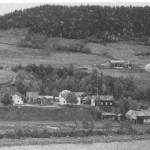 Hyttbakken ble tidlig en sentral plass. Dette bildet er fra før nyvegen ble bygd. Oppe i lia ser vi Mølnhus til venstre og Mebost til høgre, med Mølnåa som grense mellom dem.