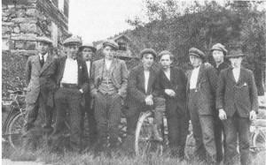 Dette bildet fra ca. 1920 viser fra v. Ole R. Rolset, Bernt J. Evjen, Ingebrigt P. Marstad, Ole O. Løvset, Mikal P. Velve, Kristian Mølnå, Ludvik Mosleth, Kristian Evjen og Peder J. Evjen, samlet ved ungdomshuset Hyttvang, som vi ser hjørnet av. I bakgrunnen Mølnå Mølle.