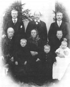 Anna Johnsdt. Lillestokke til dåpen i 1901. Bakerst: Peder, Tomas og John Lillestokke, i midten John d.e. og Agneta og Mali med dåpsbarnet, og fremst de to eldre barna, Ole og John.