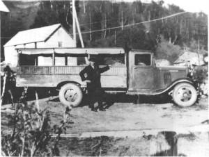 Den første lastebilen på Mosletta, Chevrolet modell 1935 var det Baro Krogstad som eide. Her er den ny med påbygd platting og overbygg for rutekjøring, utført av Brudal smie. Bildet er tatt ved handelsmann Stokke.