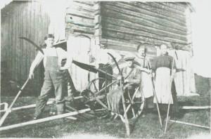 Den første slåmaskina er kommet til Solem og blir her beundret av Olaf. Gunder, John, Anne G. og Anne P. Solem.